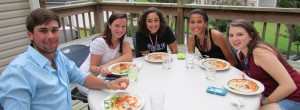 Duke Catholic students enjoy a home-cooked meal together on the back porch of the Falcone-Arena House.